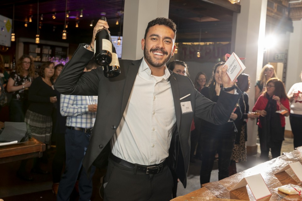 A photo of Samuel Mullin, Marketing Coordinator at Shen Milsom & Wilke LLC, at the SMPS Holiday Party holding two bottles of champagne